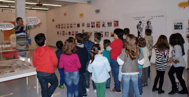 Asier y Javier muestran viñetas a niños de 6 a 12 años en la Sal Rekalde de Bilbao antes de iniciar el taller de humor gráfico